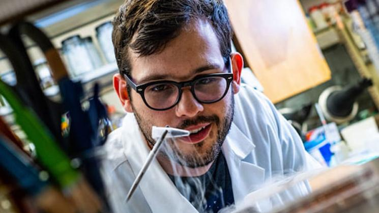 Rice University graduate student Ian Campbell pulls a vial of ferredoxin proteins from cold storage. The iron and sulfur proteins, believed to be present at the start of life on Earth, facilitate the transfer of energy in cells. The Rice experiments showed synthetic biologists may use them to control electron transfer in cells. Photo by Jeff Fitlow