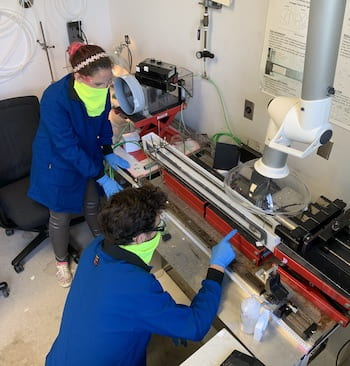 Rice University graduate students Lauren Taylor and Oliver Dewey work to refine the process of making threadlike fibers from carbon nanotubes. Their fibers now surpass the strength of Kevlar. Courtesy of the Pasquali Research Group